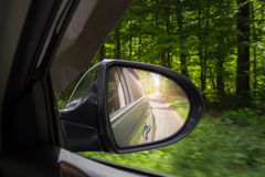 A view in the side view mirror. Mirror rear car. Reflection of the road Stock Photo