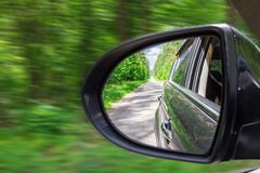 A view in the side view mirror. Mirror rear car. Reflection of the road Stock Photos