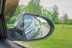 A view in the side view mirror. Mirror rear car. Reflection of the road Royalty Free Stock Photos