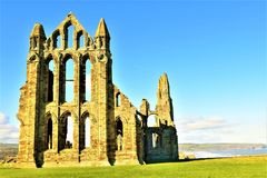 View of the side of Whitby Abbey, from the pond. Taken in late winter sunlight in the middle of the day, to reveal all the colourations of the Abbey`s stonework Stock Photo