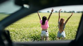 View through the side window of females in field. View through the car side window of two attractive females standing in flower's field on a summer day. Charming stock video