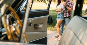 View through a window of a vintage car, through, onto a hugging couple, upon which the sun is shining.a black watch on a man`s ha royalty free stock images