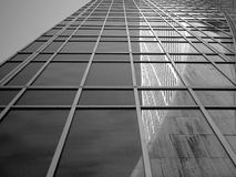 A view from the sidewalk in front of a glass sky scraper shows a reflection of the Grace building. Royalty Free Stock Photo