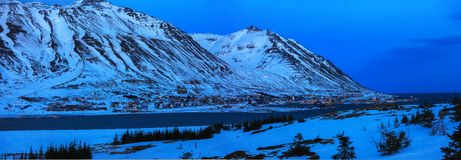 View on Siglufjordur at dusk in winter, Iceland. Siglufjordur is located in the beautiful fjord of the same name, and high and dra. Matic mountains tower over royalty free stock photos