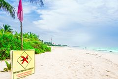 View on sign at tropical beach next to Tangalle warning of rough sea. Sign at tropical beach next to Tangalle warning of rough sea royalty free stock photo