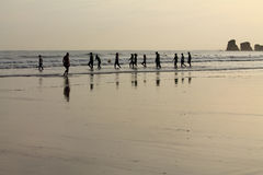 View on silhouette of group of people surfers heating up going to ocean in sunrise with reflection in water. View on silhouette of group of people surfers Stock Photo