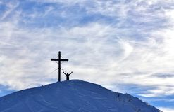 Winter Scene Mountains Men Active. View of the silhouette of wooden cross that stands in the top of a snowy hill. Next to him stands a man stock photos