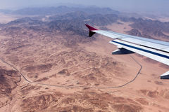 View of the Sinai Mountains from the plane. View to the Earth from a window of 10000 metres flying at height above sea level the airplane (Desert, mountains Stock Photo