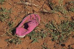 SINGLE LOST PINK SHOE IN THE SAND. View of single left sided pink tekkie type lost shoe lying on red sand stock images