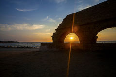 View of sinking sun through aqueduct arch Royalty Free Stock Photo