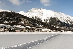 A view of a ski piste and snowy mountains and a town in the alps switzerland in winter Stock Image