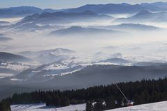 View from the ski slopes on snow covered and foggy valley on th. Top view from the ski slopes on snow covered and foggy valley on the background mountain peaks stock photo