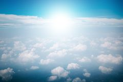 View of the sky clouds above the clouds from airplane window with sun light retro color filter. View of the sky clouds above the clouds from airplane window with royalty free stock photo