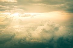 View of the sky clouds above the clouds from airplane window with sun light retro color filter.  royalty free stock image