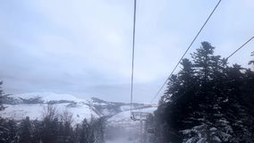 View of the sky, forest and mountains from the elevator cabin moving upwards. View of the forest, mountains and the cable car for skiers from the elevator cabin stock footage