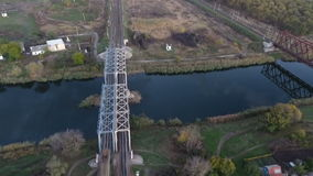 View from the sky on a freight train loaded with coal, unmanned flight over the freight train that crosses the river. Through the railway bridge, Pozdov carrier stock footage