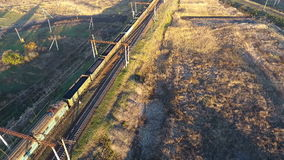 View from the sky on a freight train loaded with coal, unmanned flight over the freight train, view of a freight train. stock video