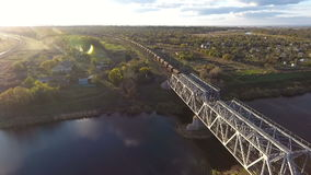 View from the sky on a freight train loaded with coal, unmanned flight over the freight train, which crosses the river. View from the sky on a freight train stock video footage
