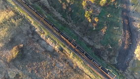 View from the sky on a freight train loaded with coal, unmanned flight over the freight train, which crosses the river stock footage