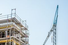 Scaffolding around the shell of a house with sky and crane in the background stock photo