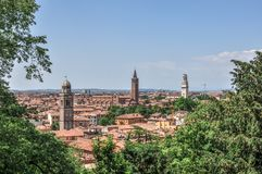 View of Verona skyline. A view of the skyline and bell-towers in Verona, Italy framed by trees stock image