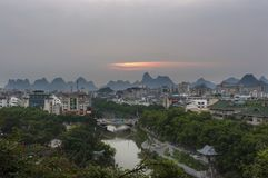 View of the skyline of the city of Guilin with the famous limestone peaks on the background at sunset, in China stock image