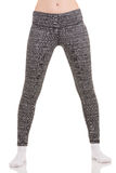 View of slim woman legs move apart to shoulders in grey patterned thermal pants in white socks Royalty Free Stock Images