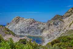 Bay between the rocks near Carloforte Island of San Pietro, Car. View of a small bay in an area of the rocky coast near Carloforte Island of San Pietro, Carbonia Royalty Free Stock Photos