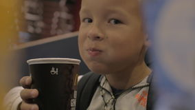 View of small boy drinking from the paper cup and smiling, fast food cafe stock footage