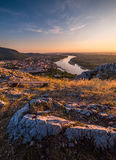View of Small City with River from the Hill at Sunset Stock Photo