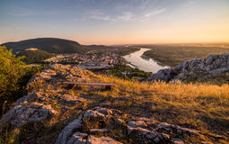 View of Small City with River from the Hill at Sunset Royalty Free Stock Image