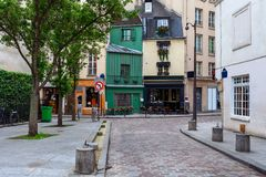 Small parisian street. View of small cobblestone street with little bar, shops and typical architecture in Paris, France Royalty Free Stock Photography