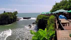 View of small exotic stony island. Small exotic stony island with cafe tables and sunshades all over coastline stock footage