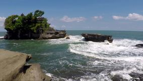 View of small exotic stony island. Small exotic stony island with cafe tables and sunshades all over coastline stock video