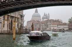 View of a small ferries on Canal Grande in a foggy day with historic Basilica di Santa Maria della Salute in the background in Ven stock photography