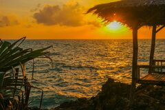View of a small hut near the ocean during sunset