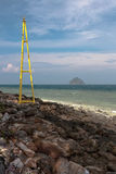 View on a small island from the rocky shore with a lighthouse in Thailand Stock Images