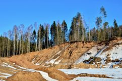View of the small mountains in the open-pit with pines and spruces in the snow in winter. This place is located in the Belarus Minsk region, the village of stock photos