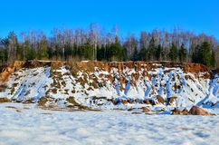 View of the small mountains in the open-pit with pines and spruces in the snow in winter. This place is located in the Belarus Minsk region, the village of royalty free stock photo