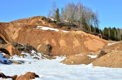 View of the small mountains in the open-pit with pines and spruces in the snow in winter. This place is located in the Belarus Minsk region, the village of royalty free stock image