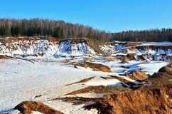 View of the small mountains in the open-pit with pines and spruces in the snow in winter. This place is located in the Belarus Minsk region, the village of royalty free stock photos
