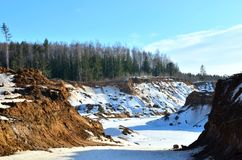 View of the small mountains in the open-pit with pines and spruces in the snow in winter. This place is located in the Belarus Minsk region, the village of stock image