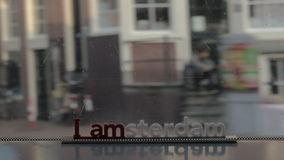 View of small plastic figure of Iamsterdam letters sculpture on the bridge against blurred cityscape, Amsterdam. View of small plastic figure of Iamsterdam stock footage
