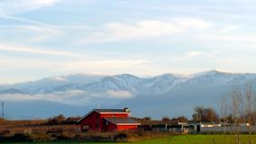 View of the small red house on a background of snow-capped mountains, with clouds lying on the tops.  stock images