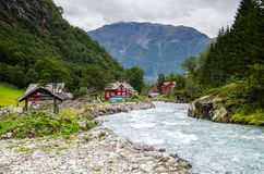 View of a small village with red houses and glacier river in Buarbreen valley in Odda region, Norway royalty free stock photography