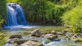 View of a small waterfall flowing stock images
