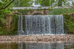 View of small waterfall in river in forest, with old bridge as background. In Portugal cascade fresh wet beautiful green flowing motion scenery wonderful relax stock photo