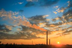 Smelter stack of a nickel plant. View of a smelter stack of a nickel plant showing the emission on the air with sunset sky as as background Royalty Free Stock Image