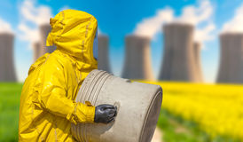 View of smoking coal power plant and men in protective hazmat suit Stock Images