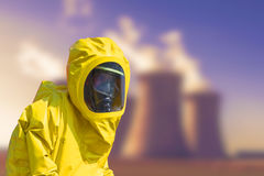 View of smoking coal power plant and men in protective hazmat suit Stock Photo